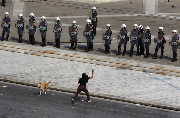 Protester hurls rocks against police during demonstration in Athens